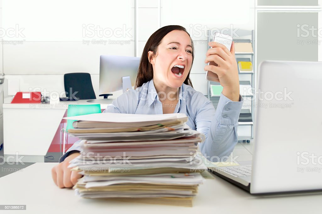 Woman screaming into phone receiver stock photo