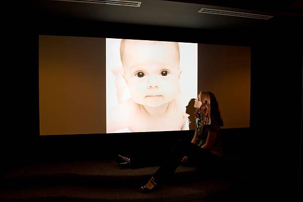 Femme de projection de photos de bébés dans Home cinéma - Photo