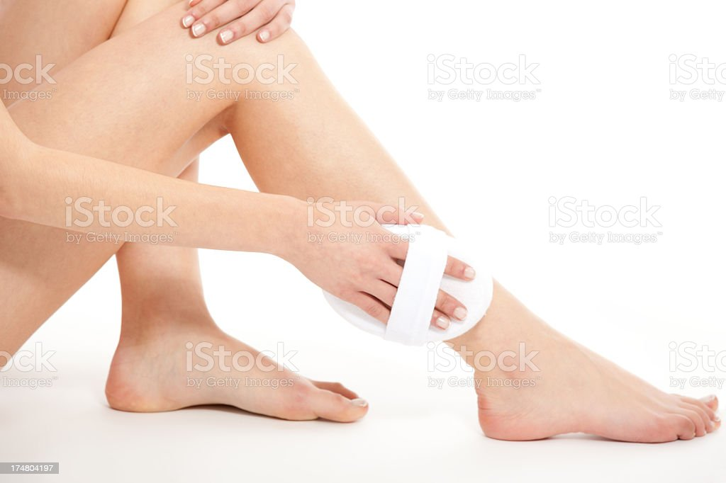 Woman scrubbing her lower leg with a loofah royalty-free stock photo