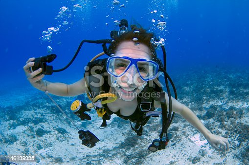 female scuba diver, using a blue mask, holding the regulator on one hand and smiling to the camera on a deep blue ocean, in Mexico (Cozumel island).