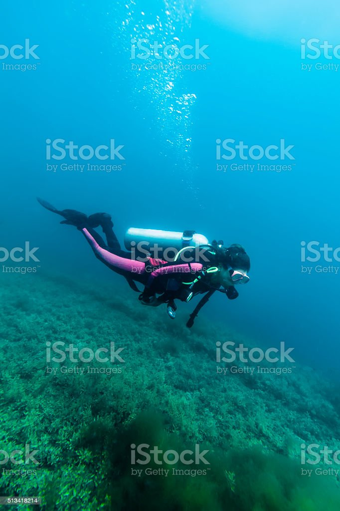 Woman Scubadiving Above the Hull of Wrecked Ship stock photo