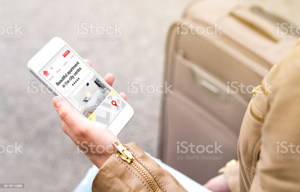 Woman search holiday apartments and rooms online with mobile phone. Vacation home rental website or application on smartphone screen. stock photo