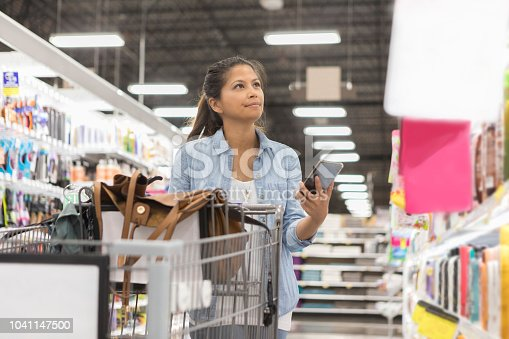 A mid adult woman purses her lips in concentration as she looks for an item on the shelf at the supermarket.  She holds up her smart phone to read her shopping list.