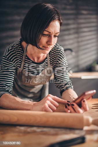 istock Woman searching apple pie recipe on the smart phone 1004508160