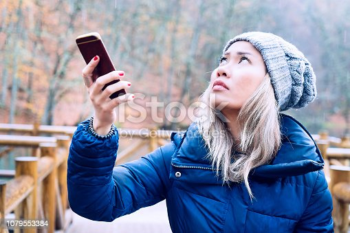 Asian woman searching for a mobile network in woods - No signal