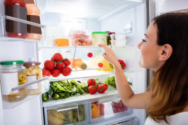 Woman Searching For Food In The Fridge Close-up Of Young Woman Searching For Food In The Fridge fridge stock pictures, royalty-free photos & images