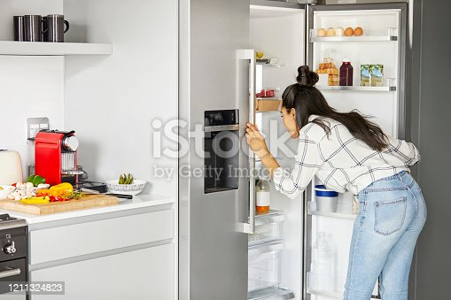 Female searching for ingredient in refrigerator. Young woman is preparing for meal. She is standing in kitchen at home.