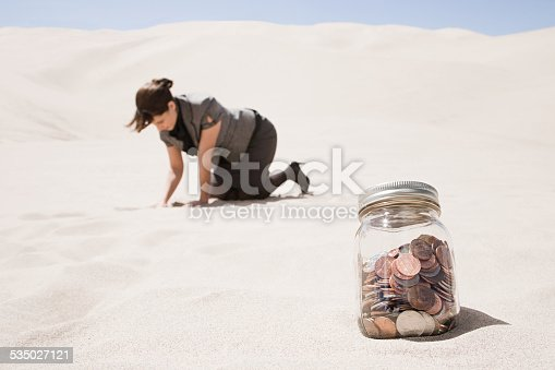 istock Woman searching for jar of coins in desert 535027121