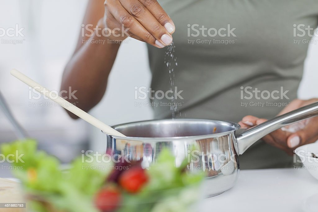 Woman seasoning her pot stock photo