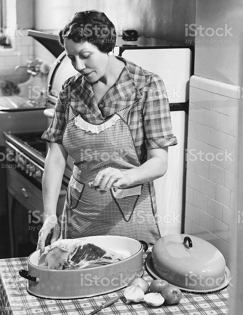 Woman seasoning meat in roasting dish (B&W) royalty-free stock photo