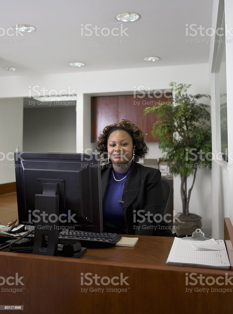 woman seated at an office desk royalty free stockfoto