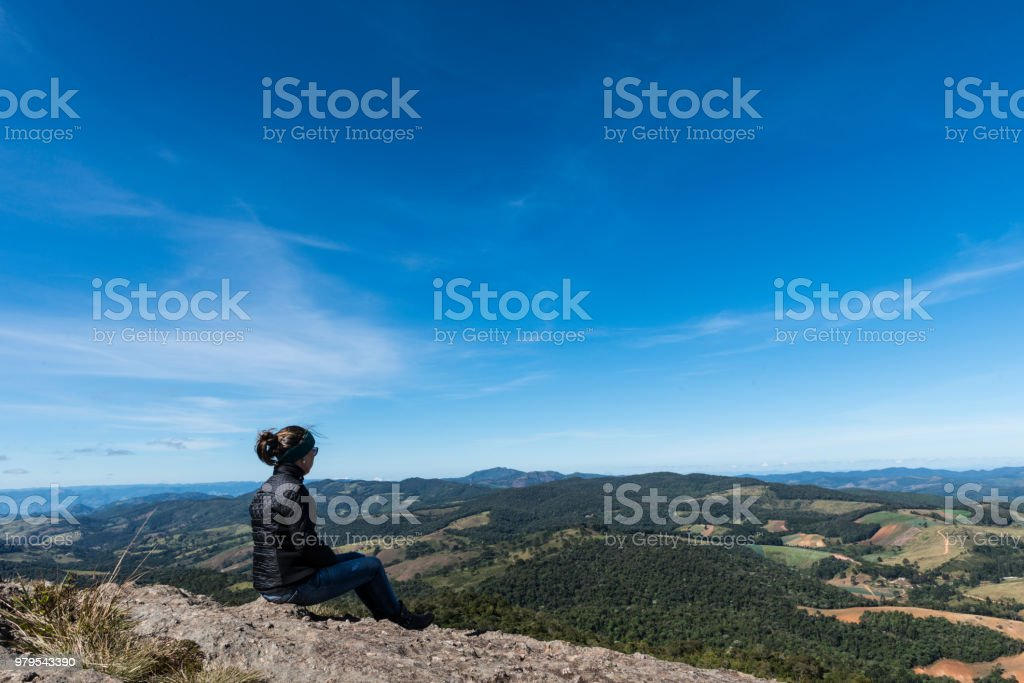 Woman seated in a rock in the São Domingos mountain, looking to the hills in a winter day, Gonçalves, Minas Gerais stock photo