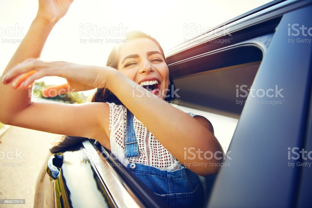 Woman seated in car waves her arms and laughs stock photo