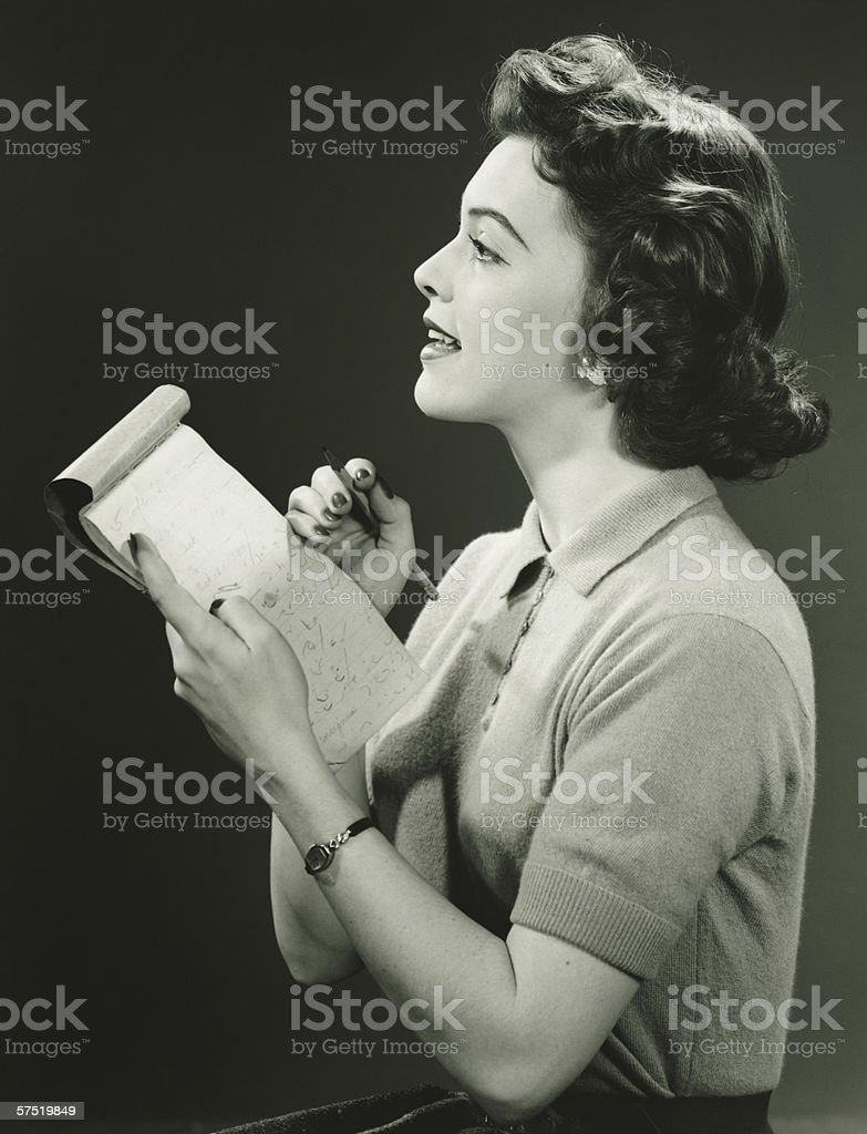 Woman secretary making notes in notebook, (B&W) stock photo
