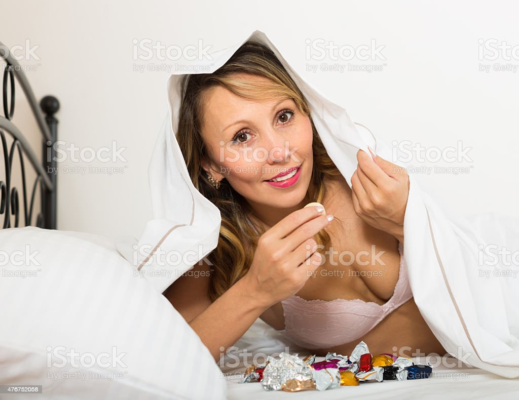 Woman secretly eating candy in bed stock photo