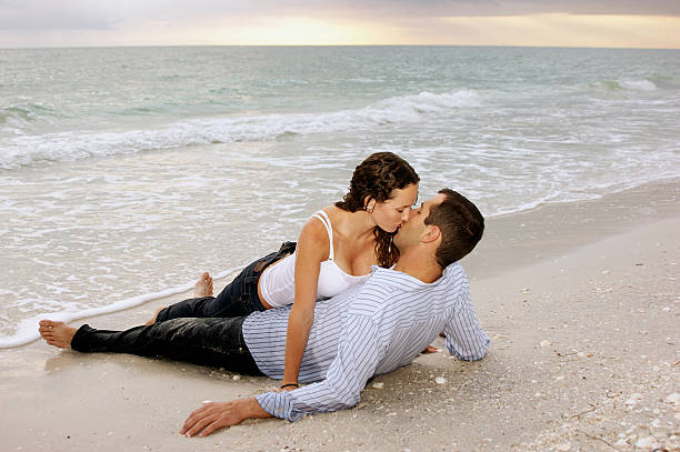 woman seducing man on beach at sunset  real couples making love stock pictures, royalty-free photos & images