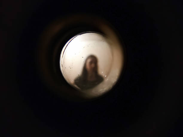 Woman seen through the peephole stock photo