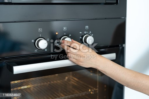 istock Woman select program turning switch at modern built in oven 1160634647