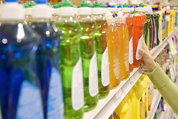 woman selecting dishwashing liquid product in supermarket - drogerie stock-fotos und bilder