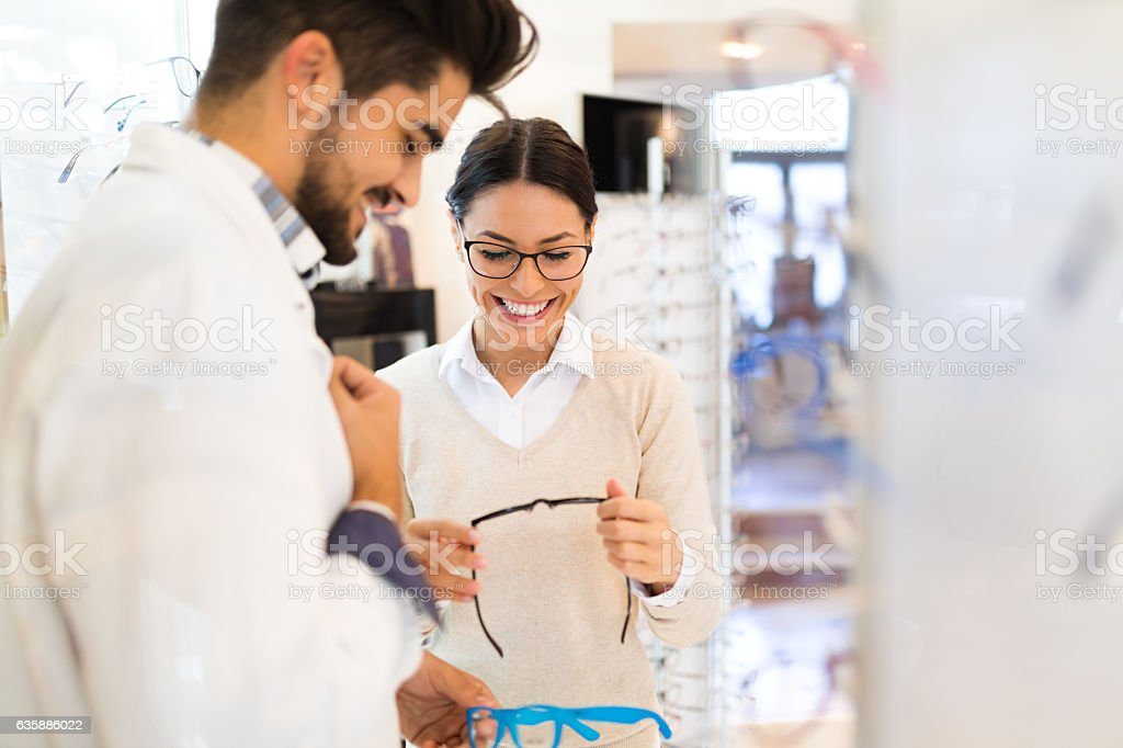 Woman selecting eyeglasses in optical store stock photo