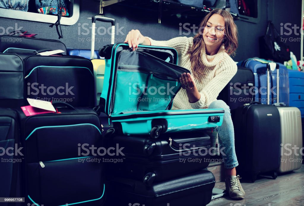 Smiling young woman selecting handy trunk in store