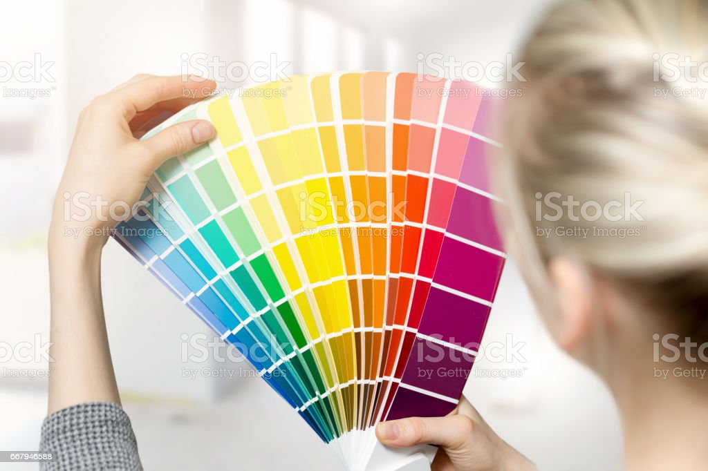woman selecting home interior paint color from swatch catalog stock photo