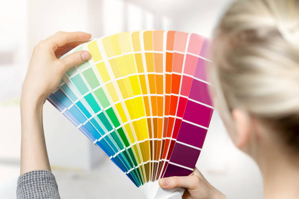 woman selecting home interior paint color from swatch catalog - choosing stock photos and pictures