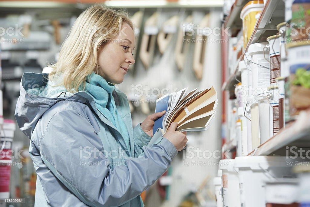 woman selecting paint at hardware store royalty-free stock photo