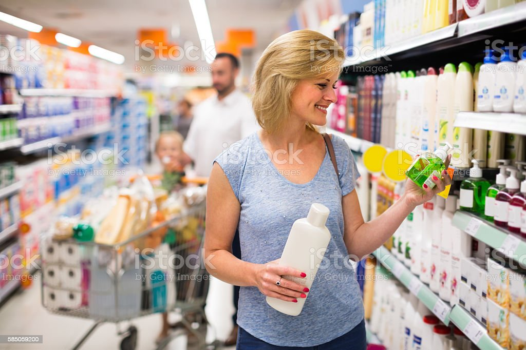 Woman selecting shampoo in supermarket stock photo