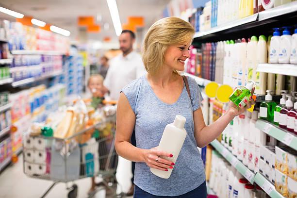 woman selecting shampoo in supermarket - drogerie stock-fotos und bilder