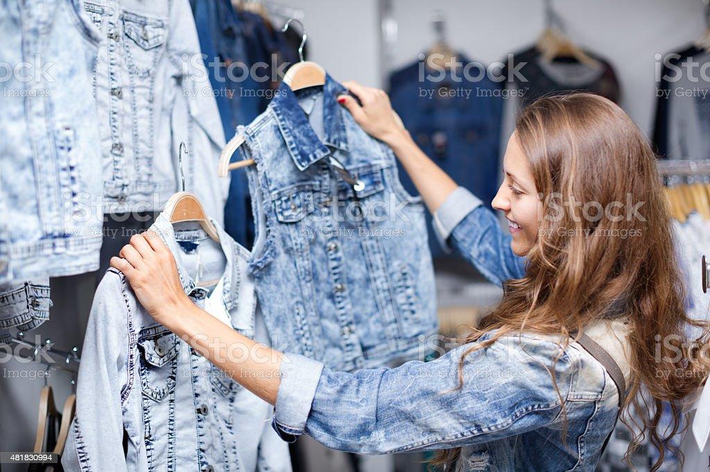 Woman selecting waistcoat stock photo