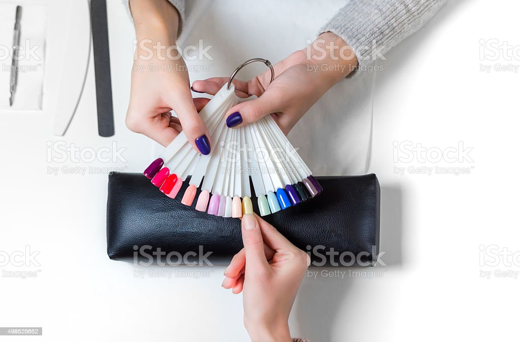Woman selects yellow color shellac for nail stock photo