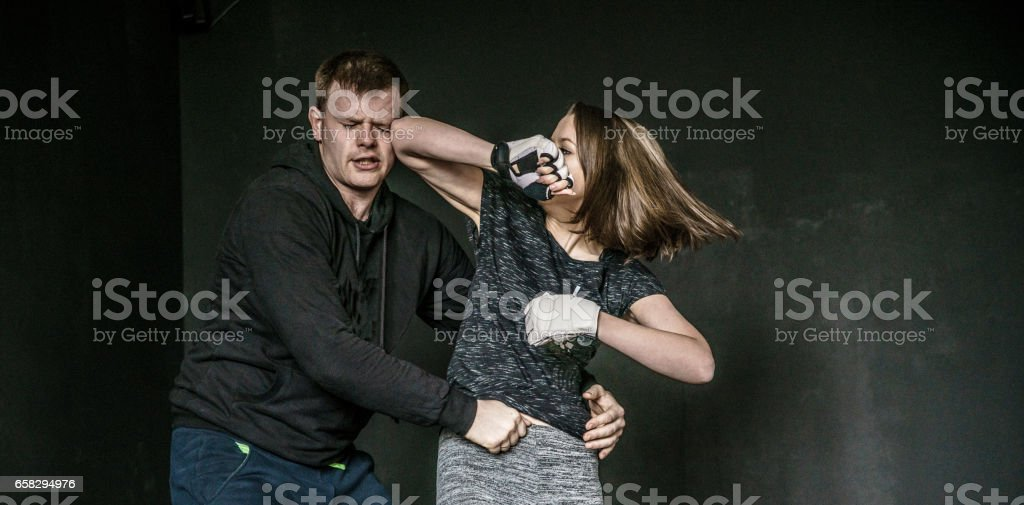 Woman self-defense trick against the man's attack. Strong women practicing self-defense martial art Krav Maga stock photo