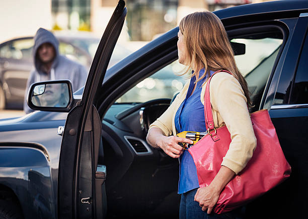 Woman Self-Defense with Handgun A woman in a car holding a handgun for self-defense. self defense stock pictures, royalty-free photos & images