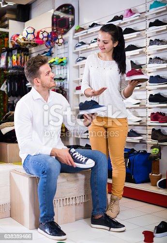 istock Woman seller assisting man in choosing sneakers 638389466