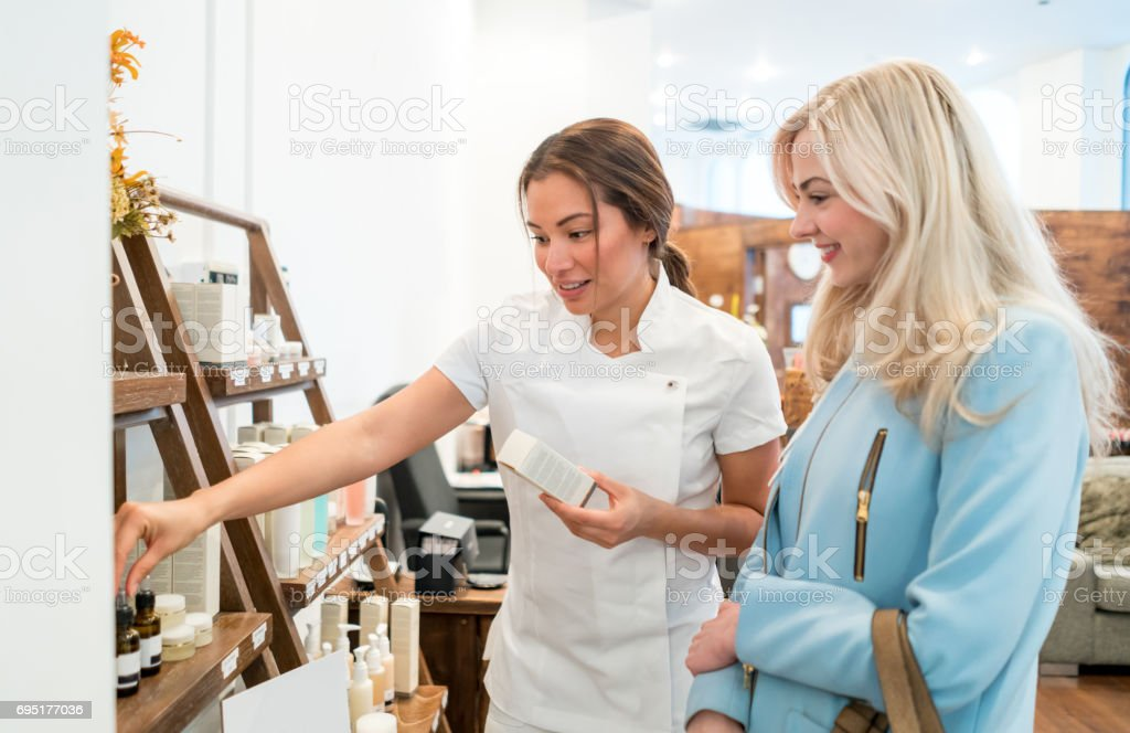 Woman selling beauty products at a store stock photo