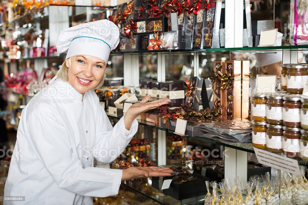 Woman selling chocolates and confectionery stock photo