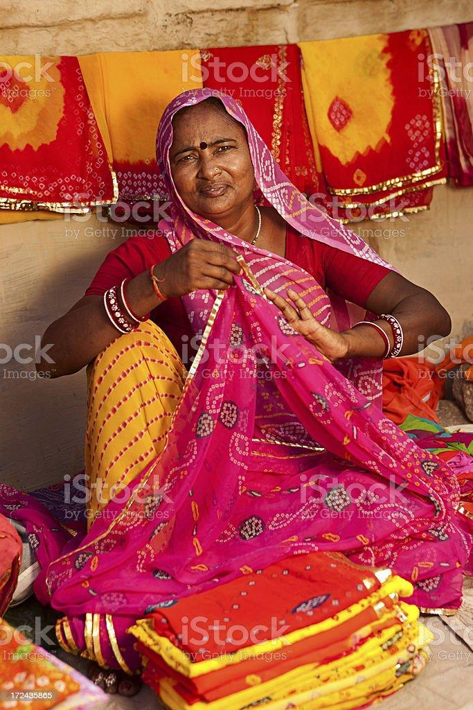 Woman selling colorful fabrics royalty-free stock photo