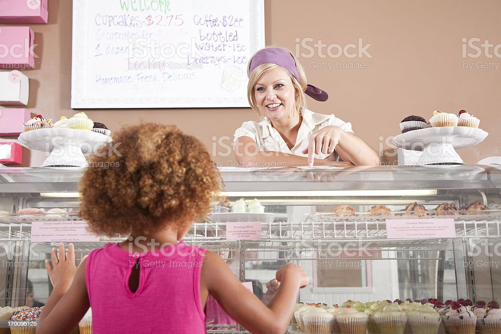 Woman selling cupcakes to little girl stock photo