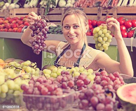 istock woman selling grapes at market 610860518