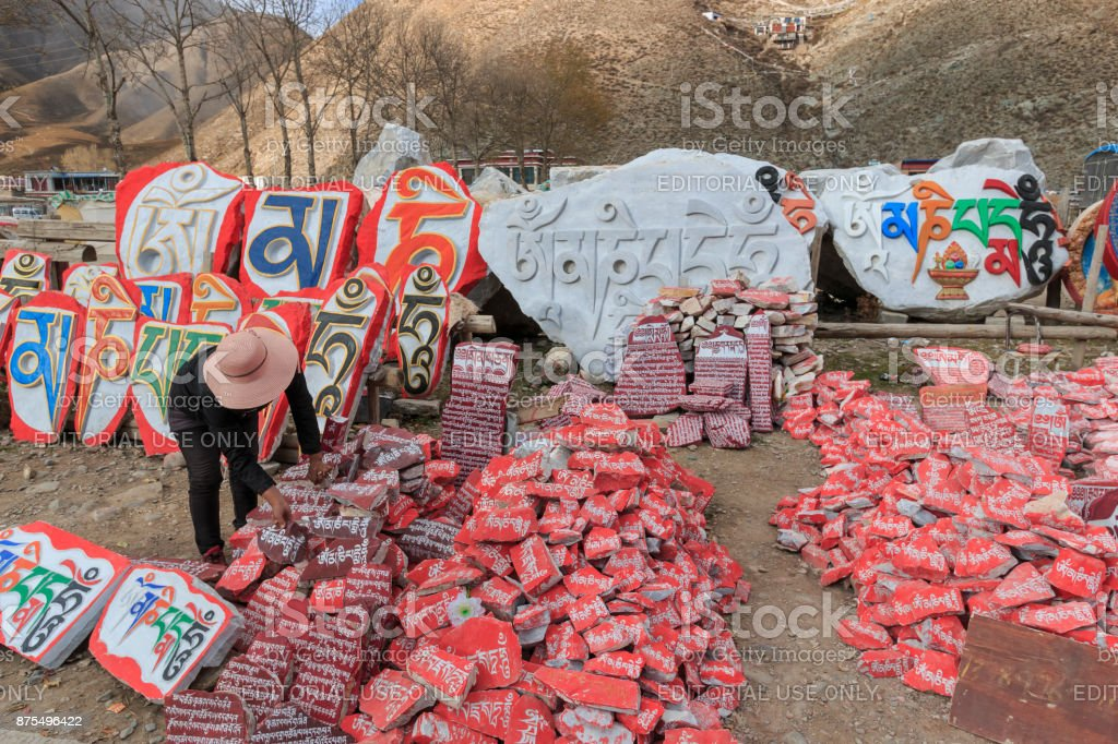 Woman selling Mani stones with buddhist mantra Om Mani Padme Hum engraved in Tibetan in Yushu, China stock photo