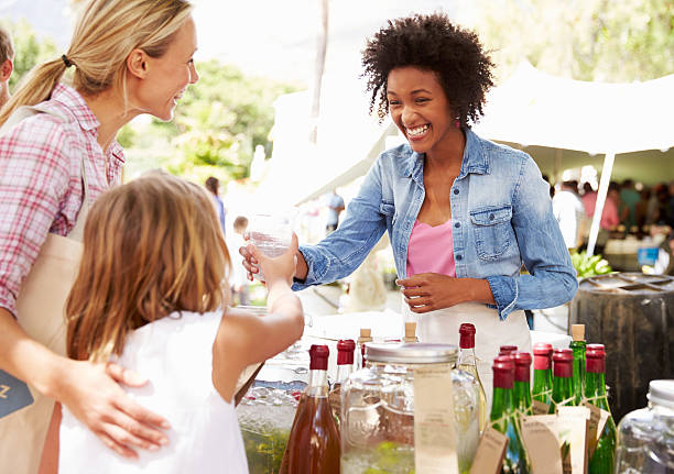 Woman Selling Soft Drinks At Farmers Market Stall stock photo