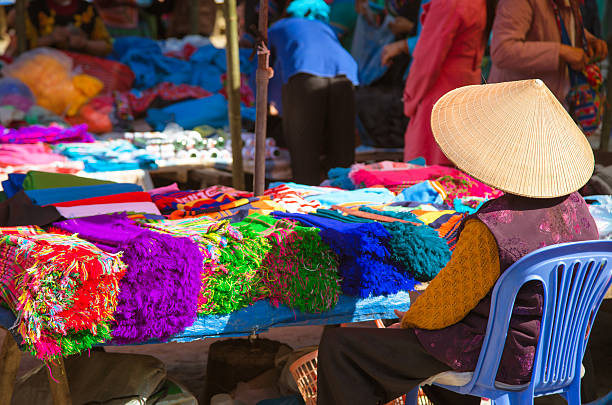 woman selling textile at Bac Ha market, Vietnam woman selling textile at the sunday market of Bac Ha in the mountains of Northern Vietnam. asian market stock pictures, royalty-free photos & images