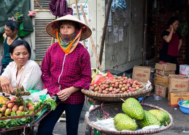 Mujer vendiendo frutas tropicales en una fruta calle de Hanoi ocupada del  mercado usan Sombreros cónicos e9a72fcc0a6