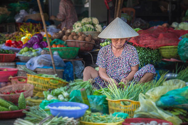 Woman selling vegetables in Hue market, Vietnam stock photo