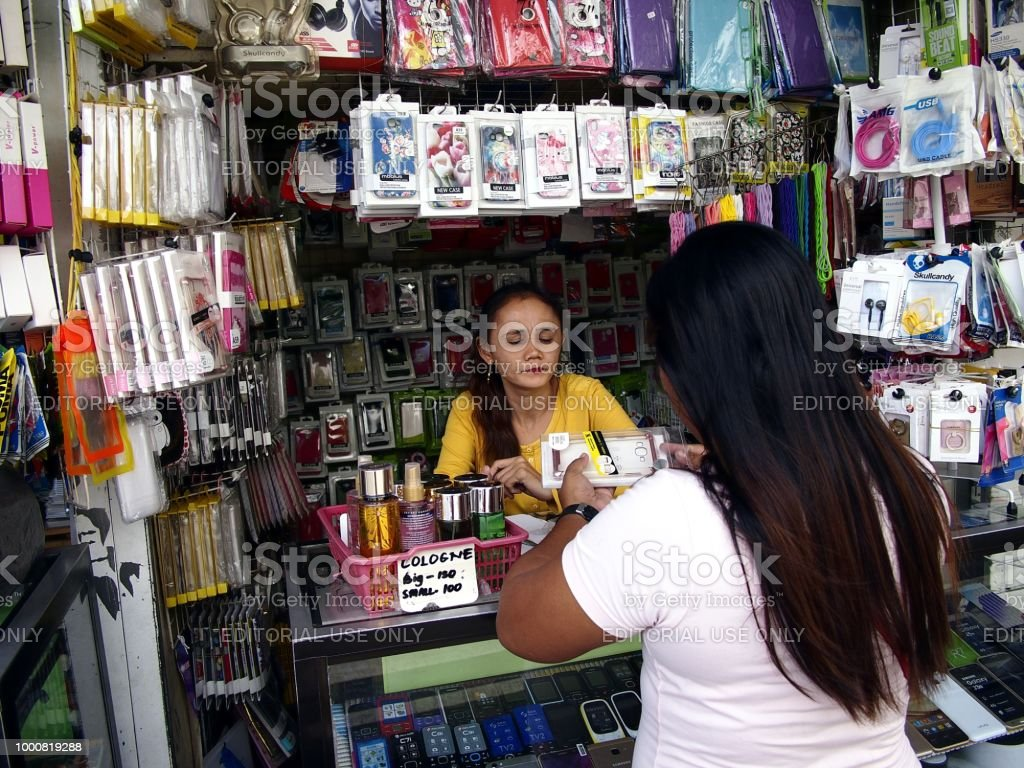A woman sells a wide variety of smartphone and accessories in her store. stock photo