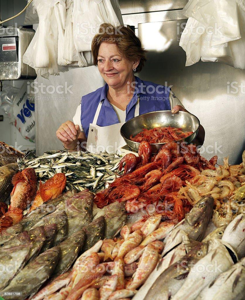 Woman sells fish at stand royalty free stockfoto