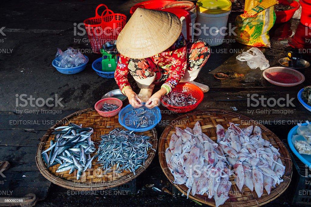 Woman sells fish at the morning market, Vietnam stock photo