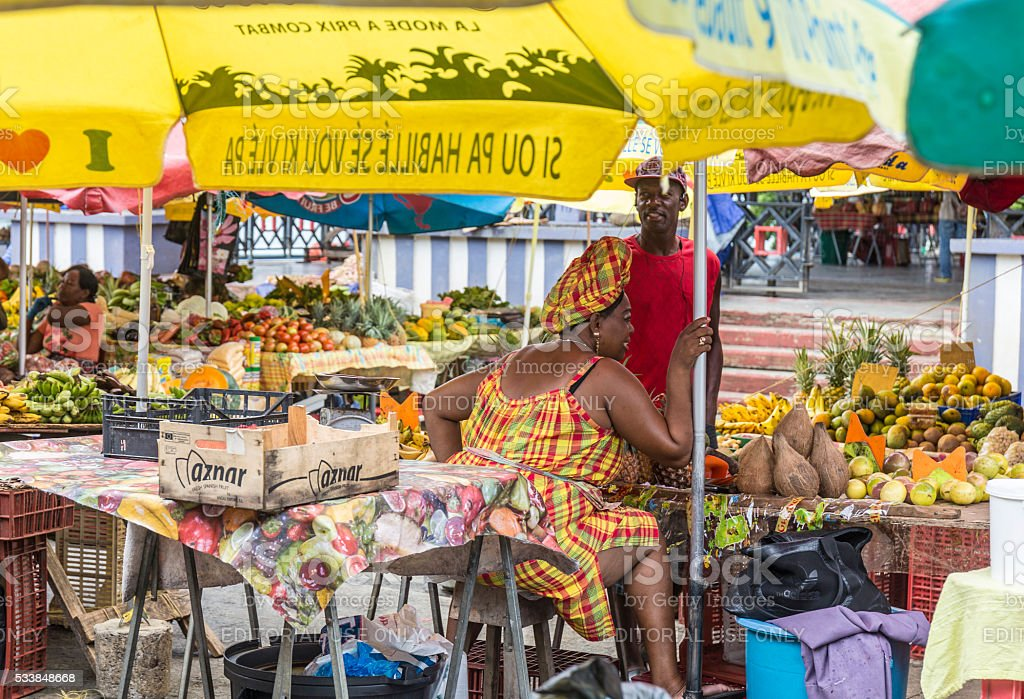 woman sells fresh fruits at the outdoor market in Guadeloupe stock photo