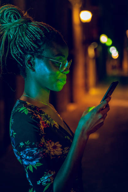 Woman sending a text message with her smartphone at night stock photo